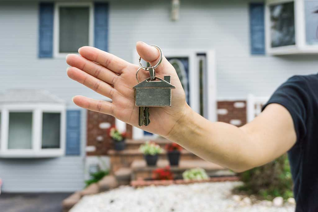 Man's hand holding keys to home with house key chain