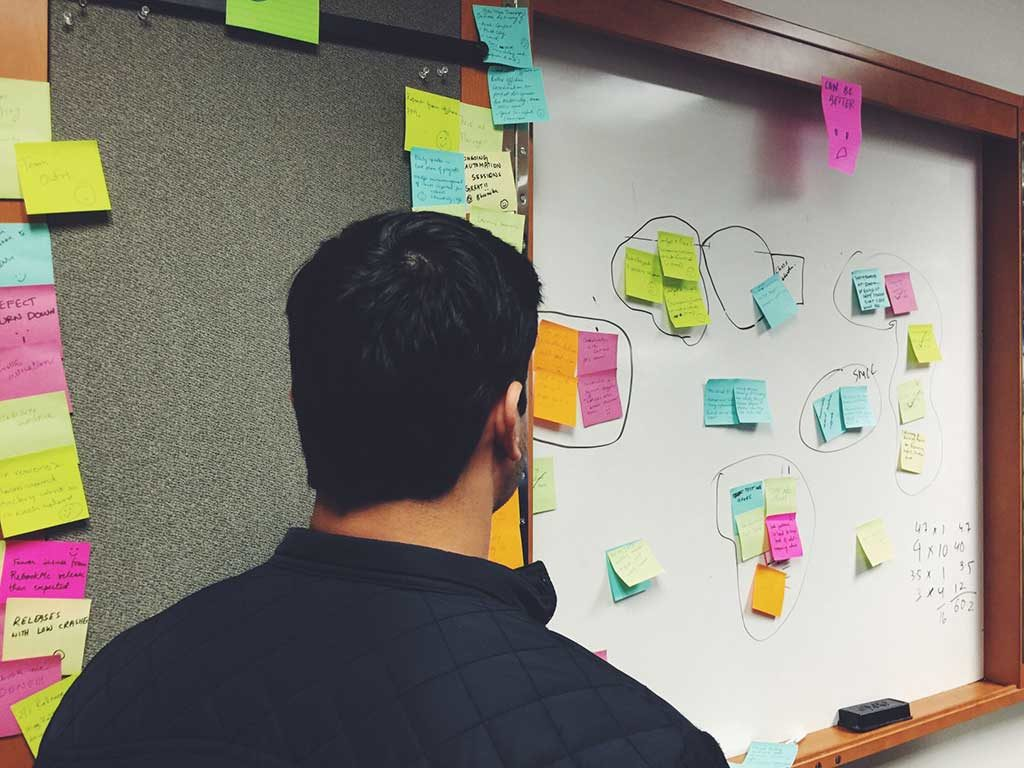 Man standing in front of whiteboard covered with different colored post it notes